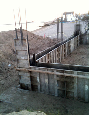 The top surface of a concrete pile cap can be seen in the lower left under a dusting of sand. The perimeter grade beam will span from pile cap to pile cap. The rebar that is projecting vertically will tie garage piers to the grade beam